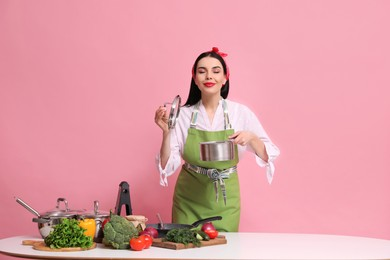 Young housewife with vegetables and different utensils on pink background