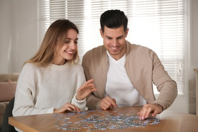 Happy couple playing with puzzles at home