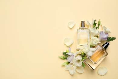 Flat lay composition with different perfume bottles and freesia flowers on yellow background, space for text
