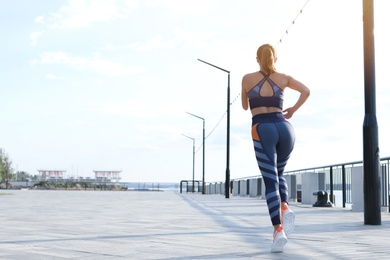 Young woman running on pier near river in morning. Space for text