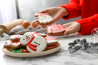 Woman holding delicious homemade Christmas cookies at white marble table, focus on plate