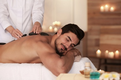 Handsome young man receiving hot stone massage in spa salon, space for text