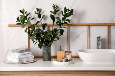 Vase with green branches, towels and soap dispenser on countertop in bathroom