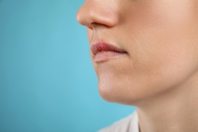 Woman suffering from herpes on light blue background, closeup. Space for text