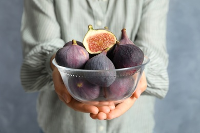 Woman holding glass bowl with tasty raw figs on light blue background, closeup