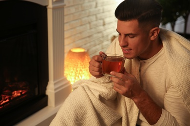 Man covered with white plaid enjoying cup of tea near fireplace