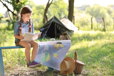 Little girl with map and book near tent outdoors. Summer camp
