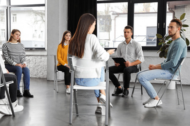 Psychotherapist working with patients in group therapy session indoors