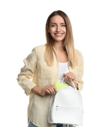 Happy young woman putting disposable menstrual pad into backpack on white background