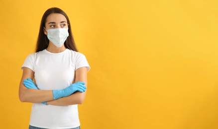 Woman wearing protective face mask and medical gloves on yellow background. Space for text