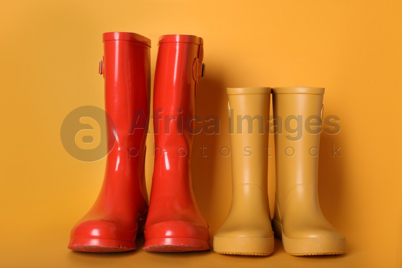 Two pairs of rubber boots on orange background