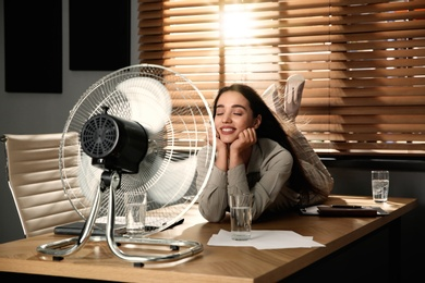 Woman enjoying air flow from fan while lying on table at workplace. Summer heat