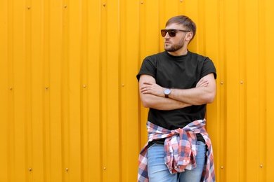 Young man wearing black t-shirt near color wall on street