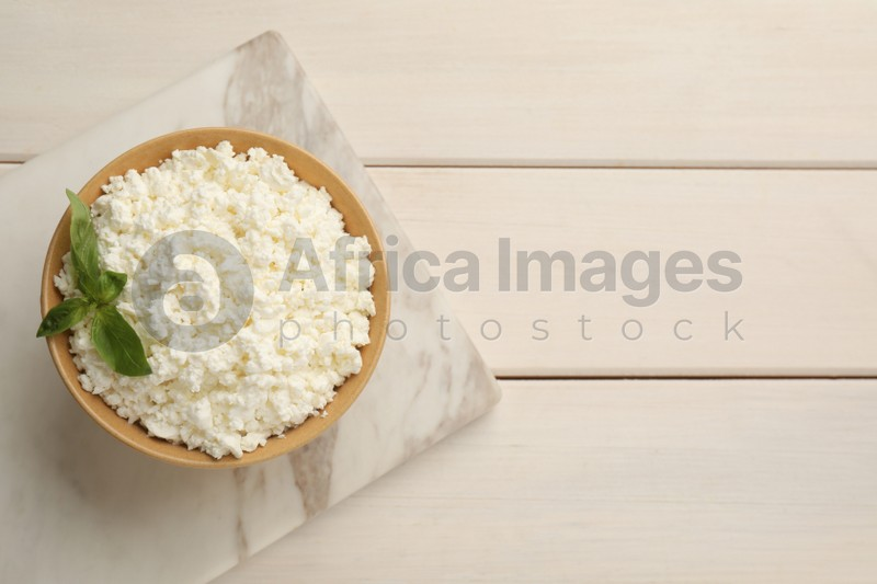 Delicious fresh cottage cheese with basil on white wooden table, top view. Space for text