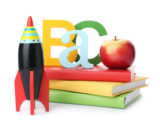 Bright toy rocket and school supplies on white background