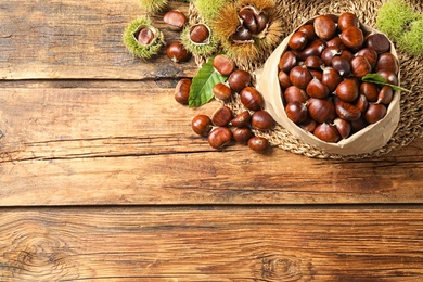 Fresh sweet edible chestnuts on wooden table, flat lay. Space for text