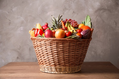 Assortment of fresh organic fruits and vegetables in basket on wooden table