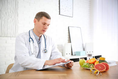 Nutritionist working at desk in his office