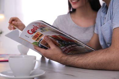 Couple reading magazine at table in kitchen, closeup