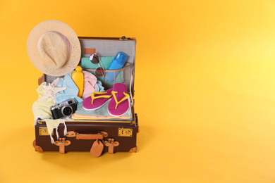 Packed vintage suitcase with different beach objects on orange background, space for text. Summer vacation
