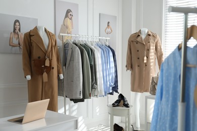 Collection of stylish women's clothes, shoes and accessories in modern boutique