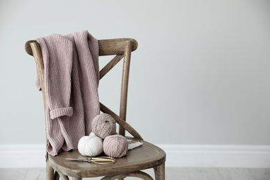 Yarn balls and scissors on wooden chair indoors, space for text. Creative hobby