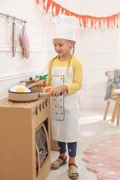 Little girl playing with toy cardboard kitchen at home