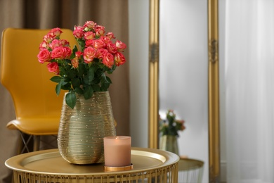 Bouquet of beautiful roses and burning candle on table indoors, space for text. Interior elements