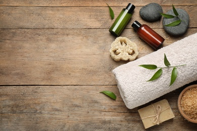 Flat lay spa composition with skin care products on wooden table, space for text