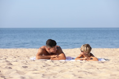Father and son lying on sandy beach near sea. Summer holidays with family