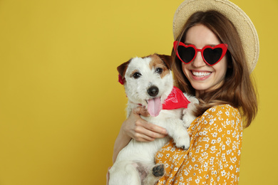 Young woman with her cute Jack Russell Terrier on yellow background, space for text. Lovely pet