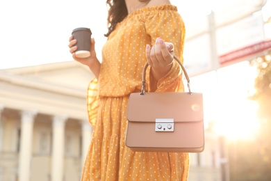 Young woman with stylish brown bag and cup of coffee on city street, closeup